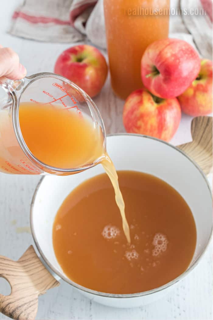 apple cider being poured into a saucepan