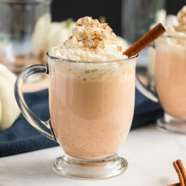 square image of pumpkin spice cocktail served in a mug with whipped cream and cinnamon
