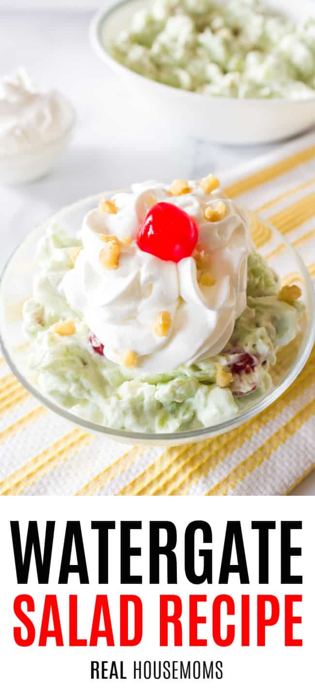 watergate salad in a serving dish garnished with whipped cream, a cherry, and nuts