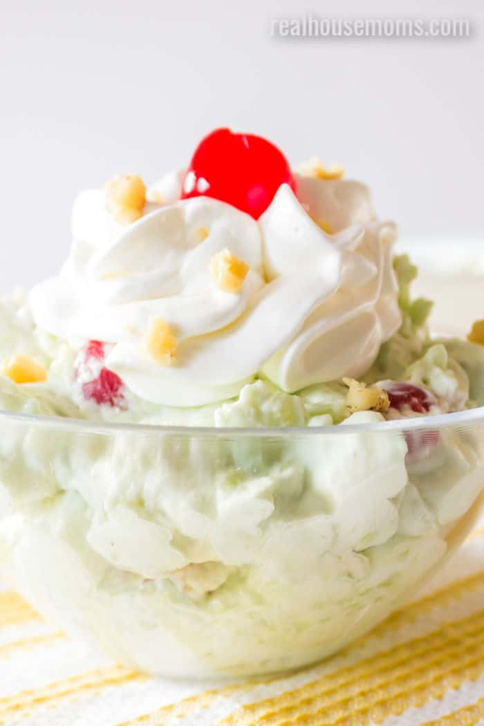 watergate salad in a bowl with whipped cream and a cherry
