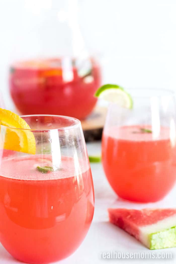 Watermelon Sangria Recipe in three glasses with a slice of watermelon on the counter