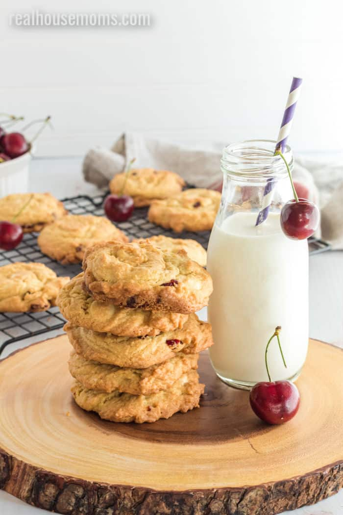 cherry pudding cookies stacked up next to a bottle of milk