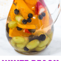 pitcher of white peach sangria with a spoon