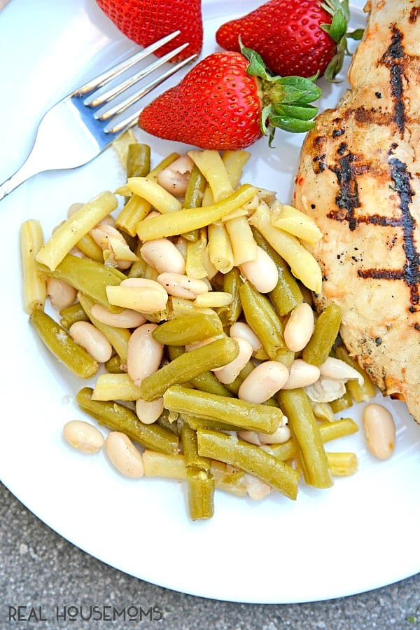 Zesty Three Bean Salad served on a plate with grilled chicken and strawberries