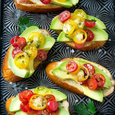 Avocado toast is not just for breakfast anymore! These AVOCADO CROSTINI are topped with a tomato and herb relish and are the perfect simple appetizer for any occasion!