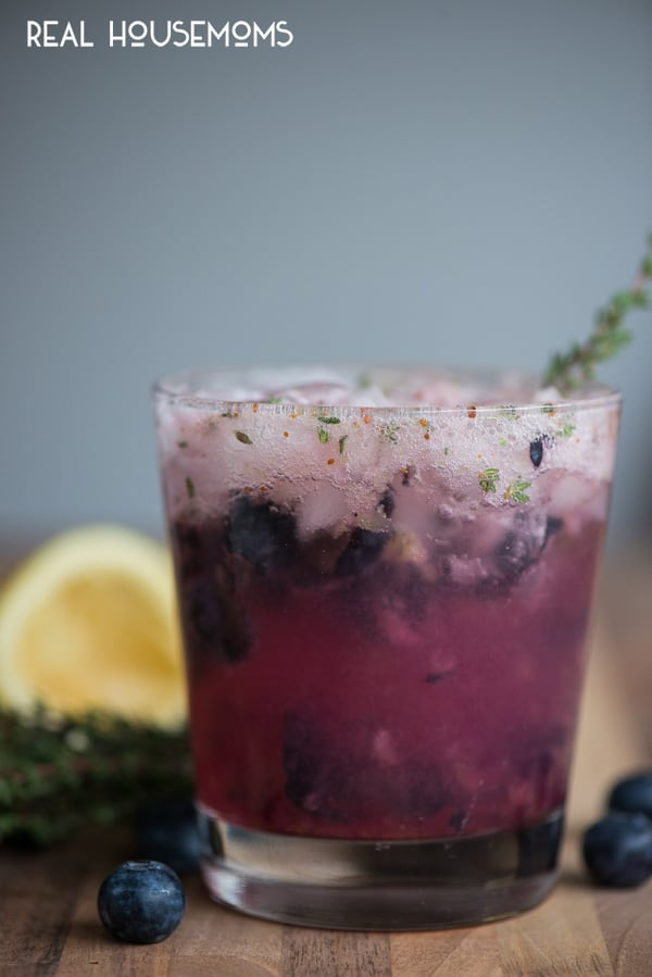 Side view of a Blueberry Thyme Crush Cocktail with thyme sprig garnish.