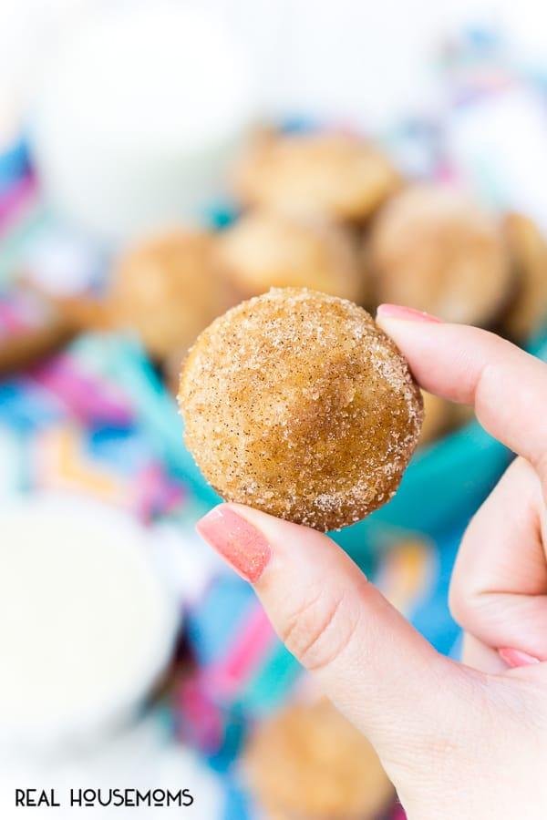 Hand holding a single Cinnamon Sugar Donut Muffin