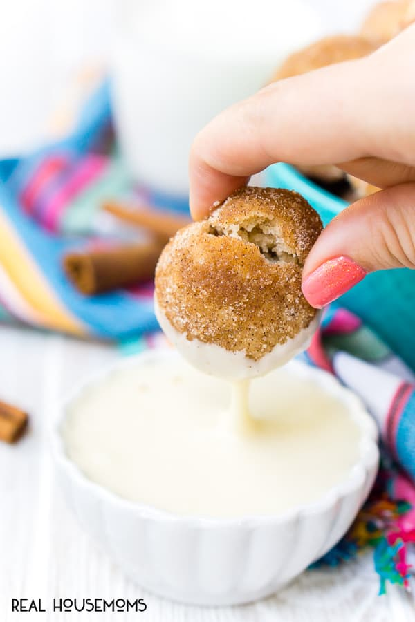 A Cinnamon Sugar Donut Muffin being dipped into vanilla icing