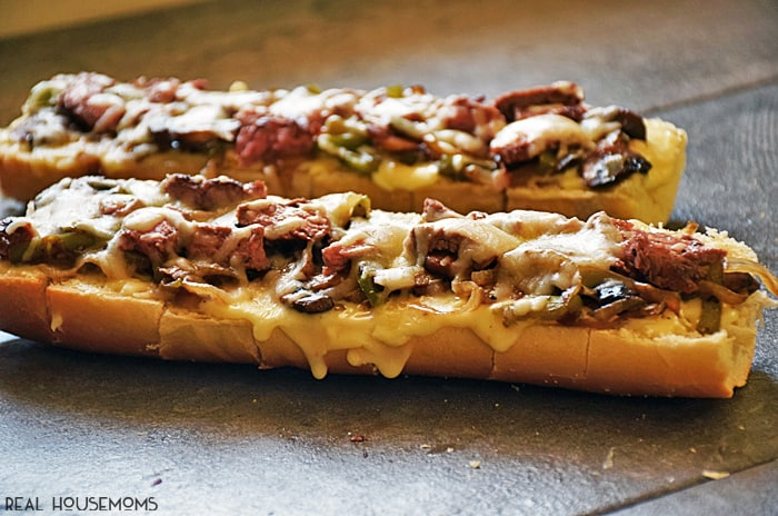 PHILLY CHEESE STEAK BREAD is an easy appetizer, dinner, or lunch recipe inspired by the traditional sandwich. This beefy, cheesy pizza bread disappears quickly, and is a snap to make!