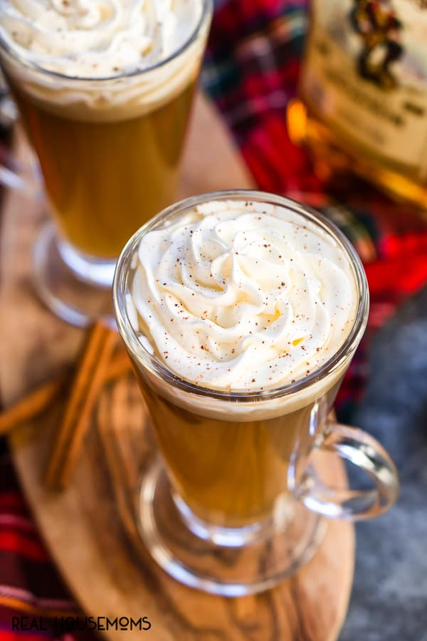 Slow Cooker Hot Buttered Rum poured into glasses and topped with whipped cream & cinnamon