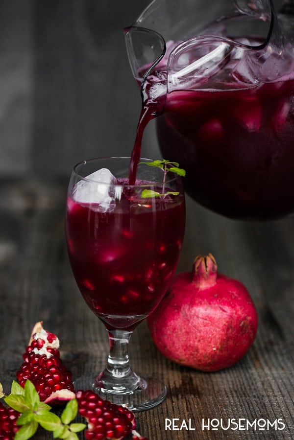 Spiked Pomegranate Punch being poured into a glass filled with ice