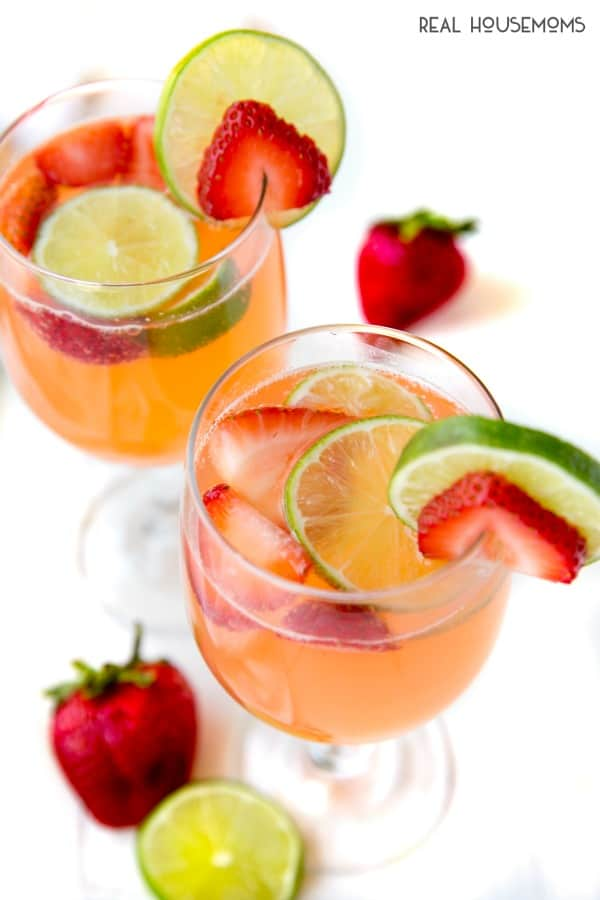 looking down into glasses of starwberry & lime moscato punch garnished with fruit