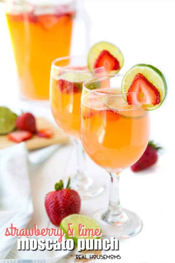 Strawberry & Lime Moscato Punch poured into wine glasses and garnished with strawberry and lime slices